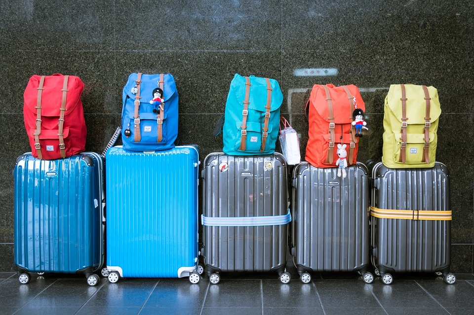 five suitcases and backpacks for family travel