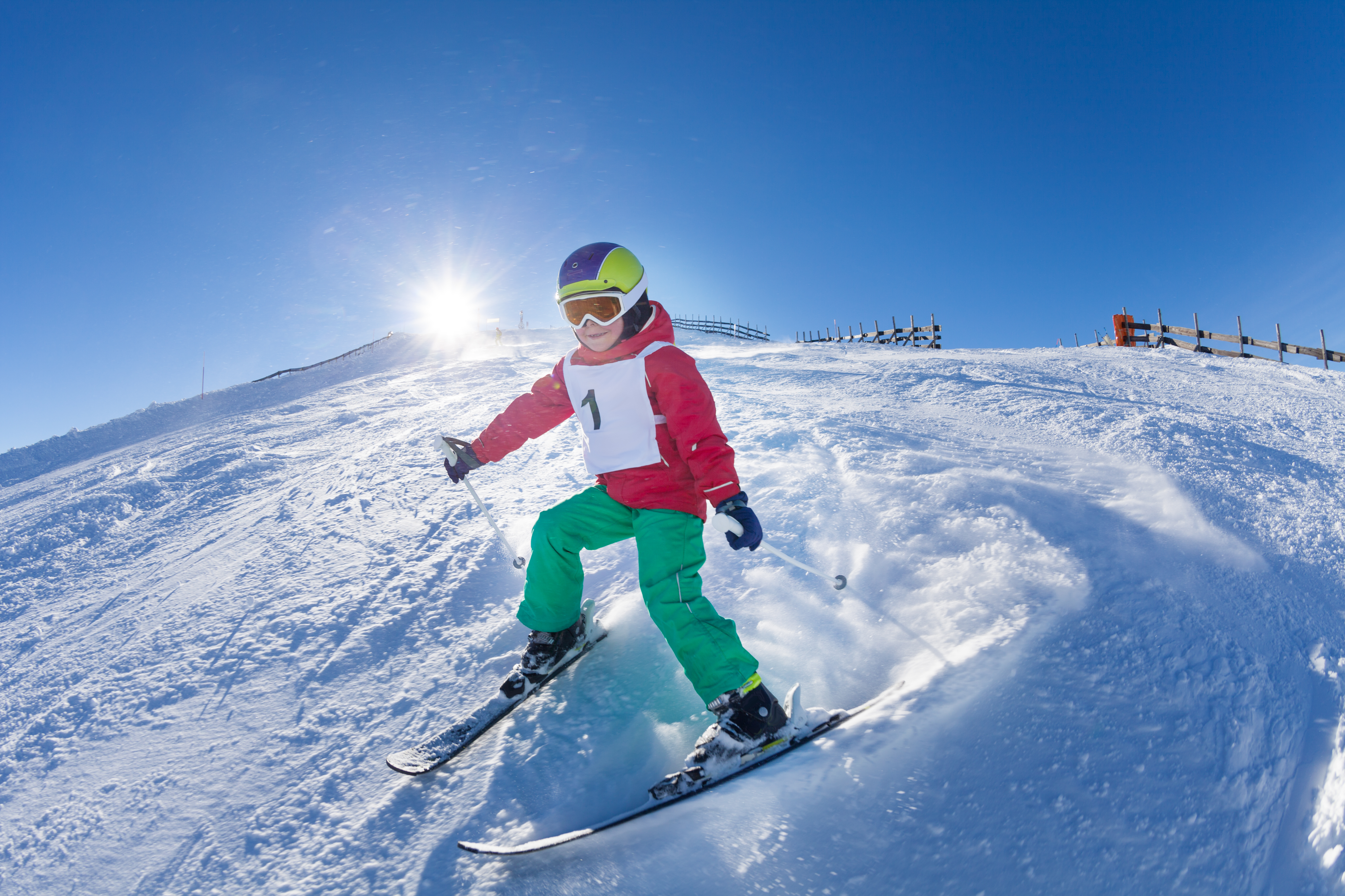 Active kid boy with safety helmet, goggles and poles skiing in mountains at sunny day