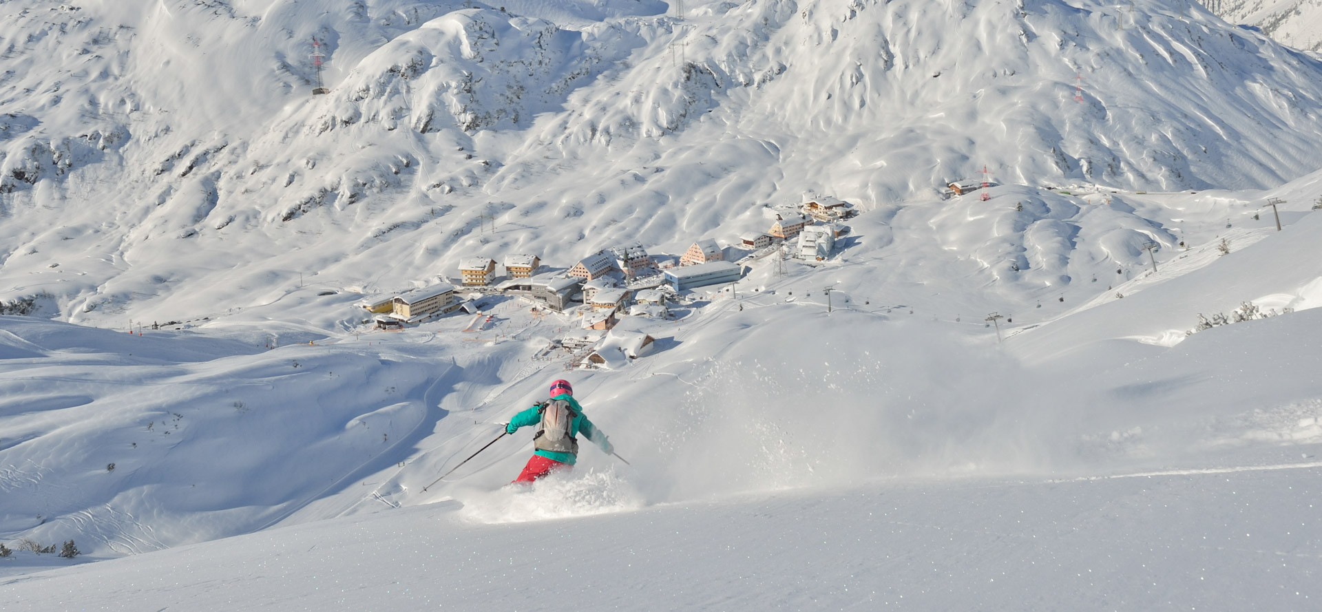 A skier in a green jacket enjoys an off-piste ski lesson on her way back towards the village of St Christophe